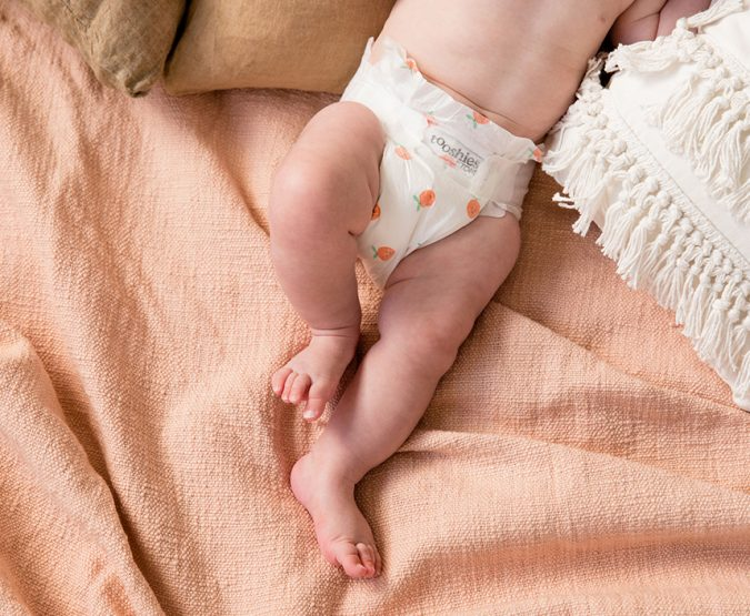 Dimpled legs of a baby wearing Tooshies by TOM organic nappies on a tangerine rug shot by Willow and Blake