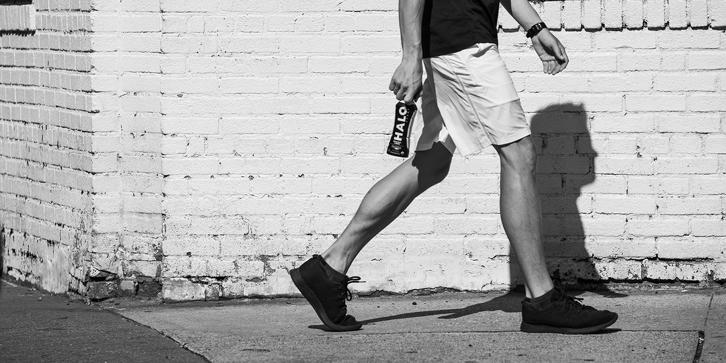 Legs of a man walking through the street holding Halo sports water in black and white