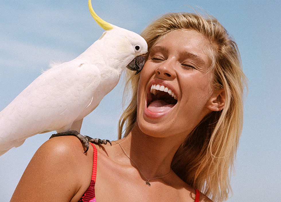 Blonde woman in Seafolly with cheeky exclamation looks at cockatoo perched on her shoulder