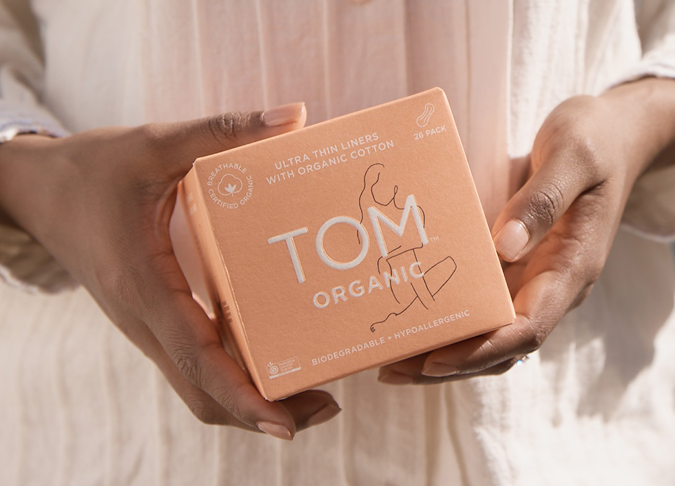 Closeup hands holding clementine coloured TOM Organic tampon box.