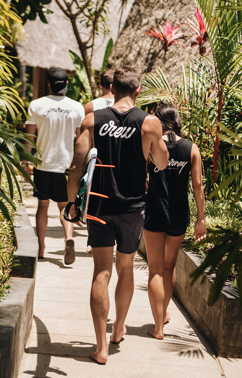 Behind shot of Journey Retreats crew heading down to surf in Bali