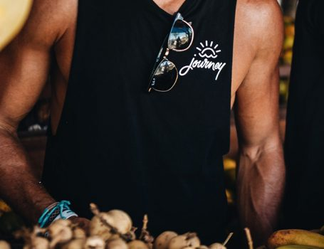 Close up of muscular tanned man in Journey Retreats black singlet and sunglasses
