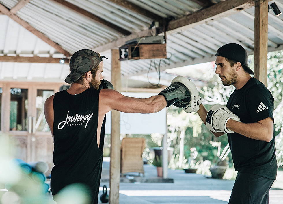 fit man in Journey Retreats singlet boxing with trainer at Bali fitness retreat