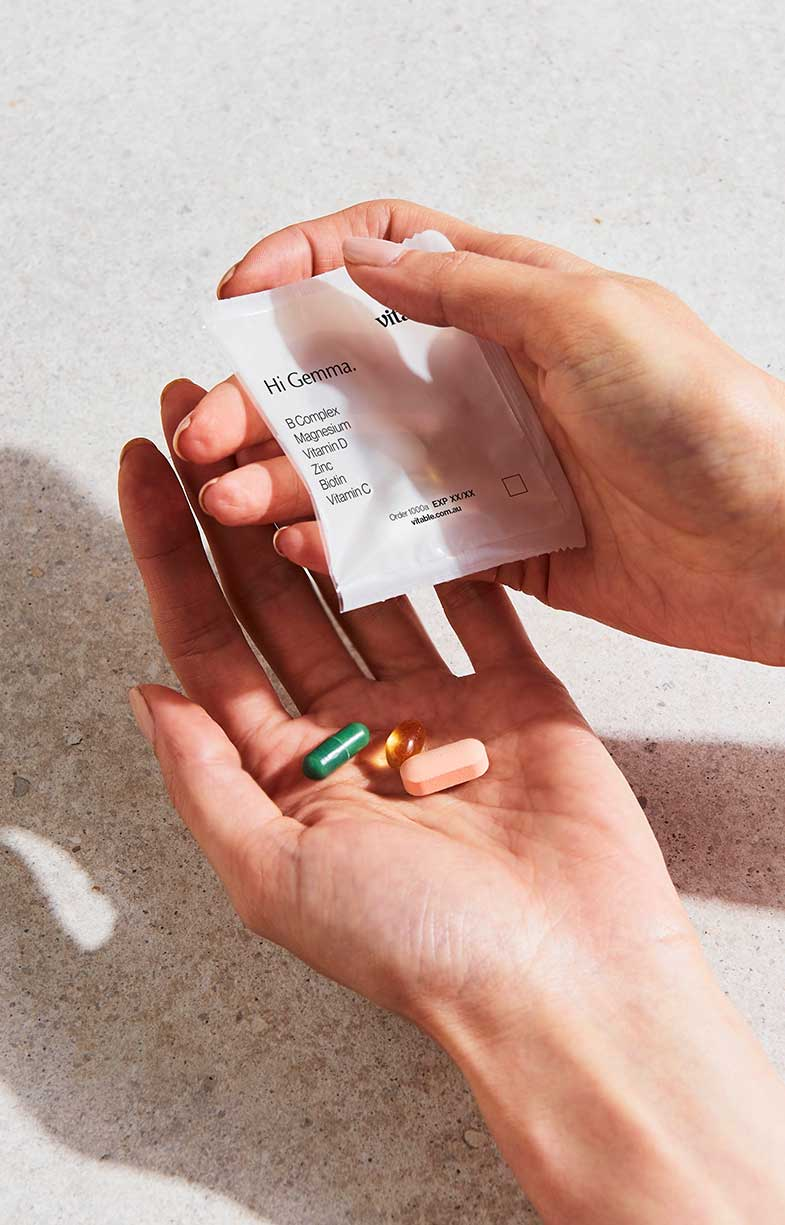 closeup aeriel shot of hands cradling an open packet of personalised Vitable vitamins